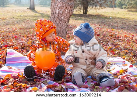 Happy child boy and girl playing with leaves in autumn park. The concept of childhood and fall. - stock photo