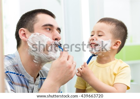 happy child boy have fun with dad shaving in the bathroom - stock photo
