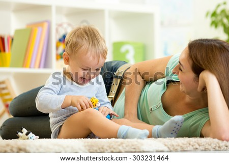 happy child boy holds animal toy playing with mom in nursery - stock photo