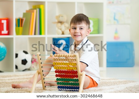 happy child boy playing with abacus toy in nursery - stock photo