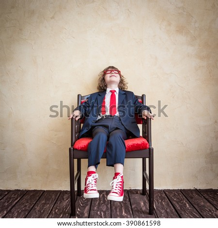 Happy child businessman relaxing. Success in business concept