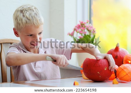 Happy child, caucasian boy, carving pumpkin for halloween - stock photo