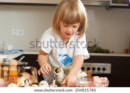 Happy child cooking soap in kitchen