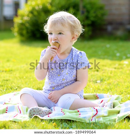 Happy child, cute smiling toddler girl, eating ice-cream sitting in summer garden - stock photo