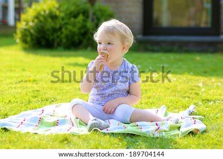 Happy child, cute smiling toddler girl, eating ice cream sitting in summer garden - stock photo