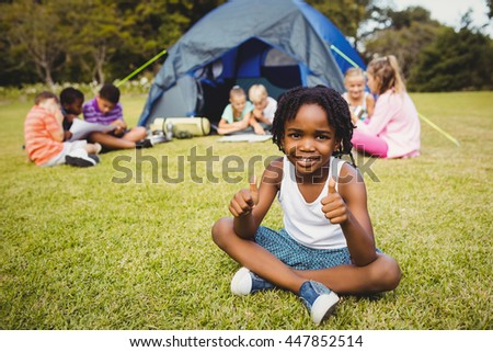 Happy child doing thumbs up during a sunny day at park - stock photo