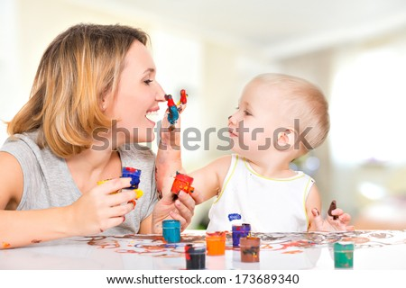 Happy child draws on the face of his mother -  at home. - stock photo
