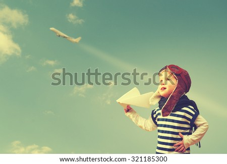Happy child dreams of becoming a pilot aviator and plays with planes in the sky - stock photo