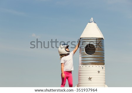 Happy child dressed in an astronaut costume playing with hand made rocket. Tinted photo - stock photo