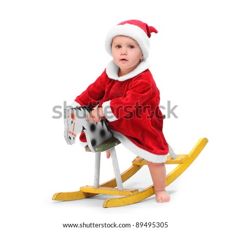 Happy child dressed in Santa Claus costume on a rocking horse.