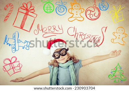 Happy child dressed in Santa Claus hat. Kid pilot playing at home. Drawn airplane on grange wall background. Retro toned - stock photo