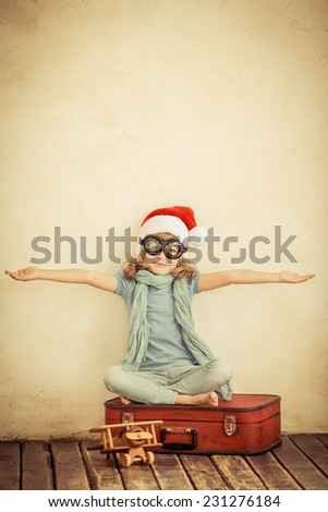 Happy child dressed in Santa Claus hat. Kid playing with toy airplane at home. Retro toned - stock photo