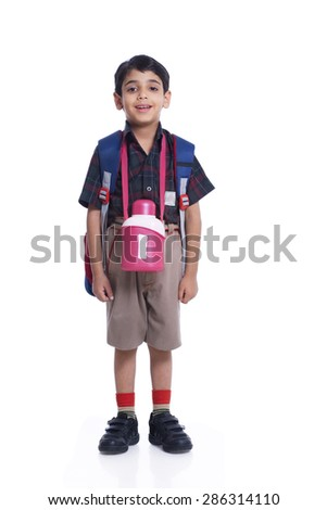 Happy child dressed in school uniform standing against white background - stock photo