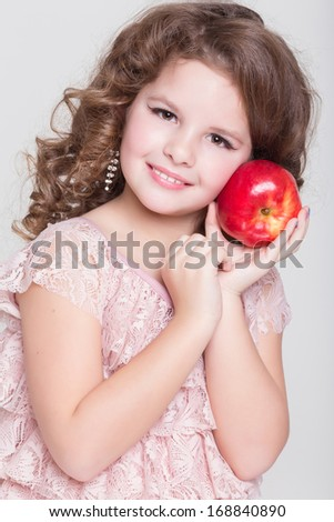 Happy child eating apples healthy organic food, little girl with red apple, isolated. Beautiful baby girl eating fruit. Kid hold red apple. Studio. white background.