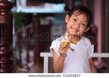 Happy child eating banana fruit. healthy food eating concept.Selective Focus