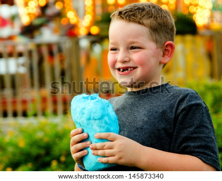 Happy child eating cotton candy at carnival - stock photo