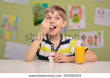 Happy child eating healthy snack and drinking orange juice - stock photo