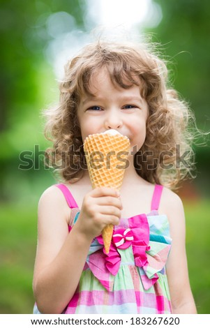 Happy child eating ice cream outdoors in summer park - stock photo