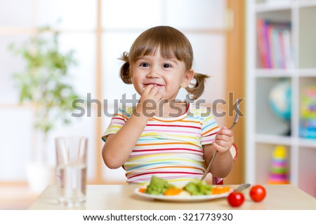 Happy child eats vegetables sitting at table in nursery - stock photo
