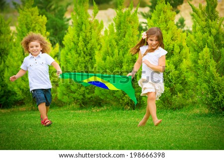 Happy child enjoying football championship, brother and sister running with big Brazil flag, active and sportive childhood concept - stock photo