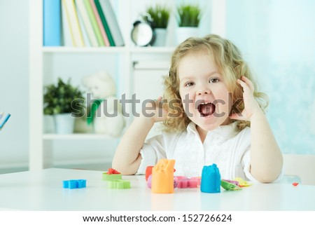 Happy child enjoying herself while modeling with colorful clay - stock photo
