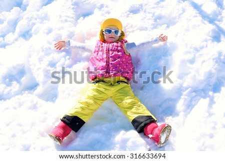 Happy child enjoying winter holidays in Alpine resort in Austria. Little girl playing in the snow. Active sportive toddler learning to ski. Kids having fun outdoors.  - stock photo