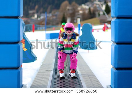 Happy child enjoying winter vacation in Alpine resort in Austria. Active sportive toddler girl learning to ski. Kid having fun in ski school going up to the slope on the magic carpet lift.