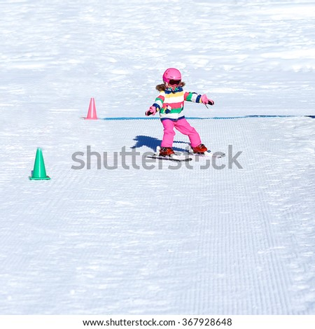 Happy child enjoying winter vacation in Alpine resort in Austria. Active sportive toddler girl learning to ski. Kid having fun in ski school sliding snowplow and turning left and right. - stock photo