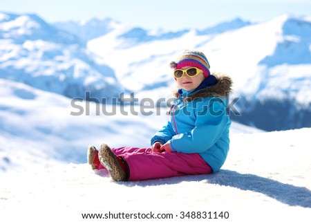 Happy child enjoying winter vacation in Alpine resort in Austria. Little girl playing in the snow. Active sportive toddler learning to ski. Beautiful Alps mountains in the background. - stock photo