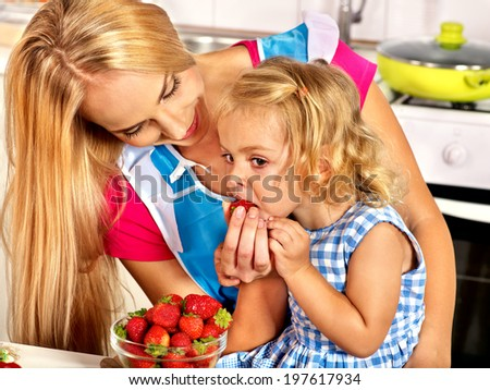 Happy child feed mother  at kitchen. - stock photo