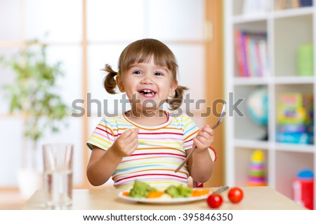 Happy child girl eating vegetables. Healthy nutrition for kids - stock photo