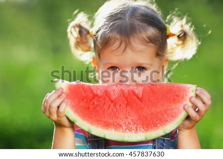 Happy child girl eats watermelon in the summer - stock photo