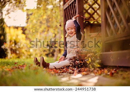 happy child girl having fun and playing with leaves on the walk in sunny autumn garden - stock photo