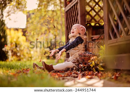 happy child girl having fun and throwing leaves in sunny autumn garden - stock photo