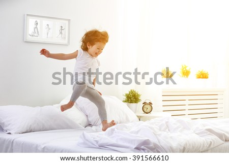 happy child girl having fun jumps and plays bed - stock photo