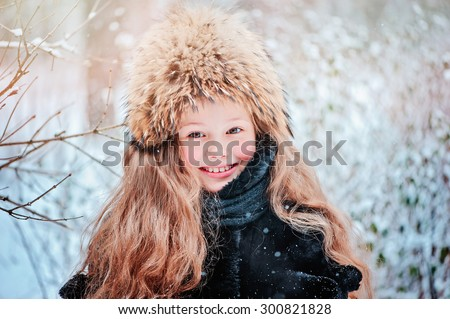 happy child girl head shot on the walk in winter forest in fur hat