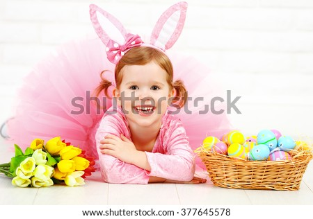 Happy child girl in a costume Easter bunny rabbit with basket of eggs and flowers tulips - stock photo
