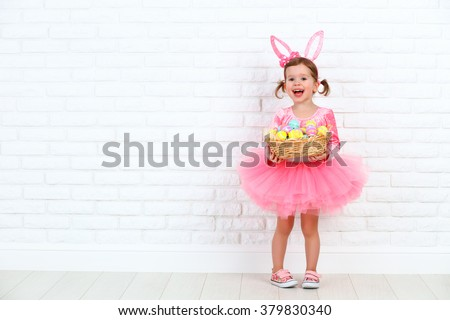 Happy child girl in a costume Easter bunny rabbit with ears and a basket of eggs - stock photo