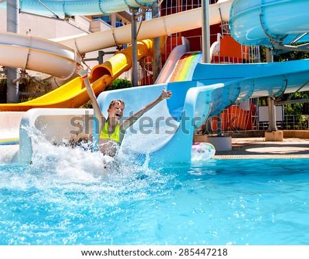 Happy child girl in bikini sliding water park. - stock photo