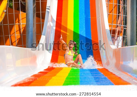 Happy child girl in bikini sliding water park. Gesture thumb up. - stock photo