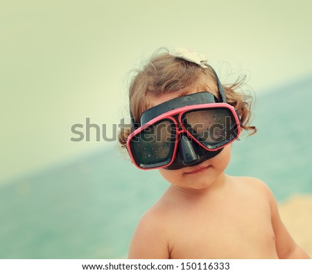Happy child girl in diving mask smiling on beach background. Vintage closeup portrait