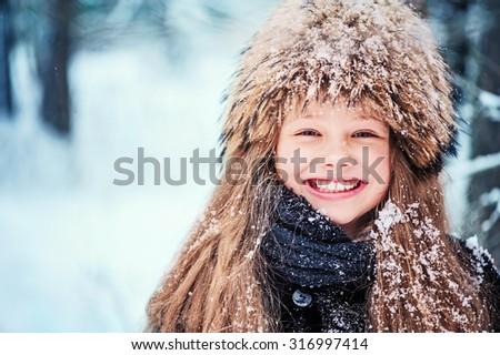 happy child girl in fur hat portrait on the walk in winter forest