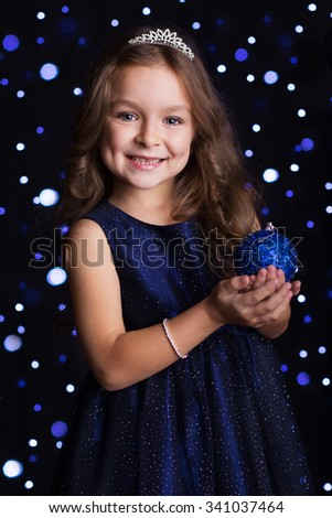 Happy child girl is holding blue Christmas tree toy in hands over background scene with lights, New years - stock photo