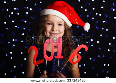 Happy child girl is holding numbers 2016 in hands in a studio over background scene with blue lights for a holiday concept. - stock photo