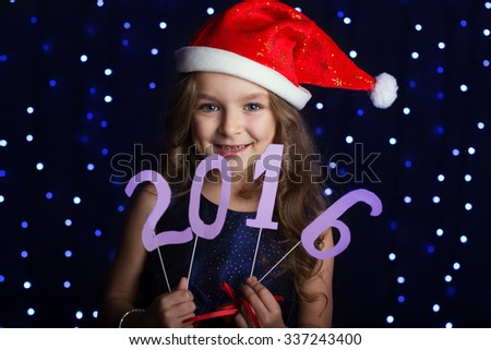 Happy child girl is wearing red santa hat holding paper digits 2016 in hands in a studio over background scene with blue lights for a holiday concept. - stock photo