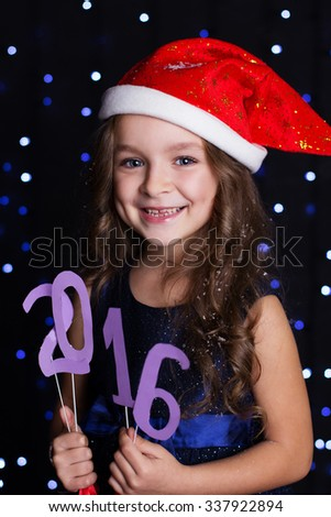 Happy child girl is wearing red santa hat holding paper digits 2016 in hands in a studio over background scene with blue lights, christmas time - stock photo