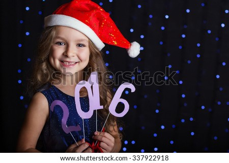 Happy child girl is wearing red santa hat holding paper digits 2016 in hands in a studio over background scene with blue lights, new year - stock photo