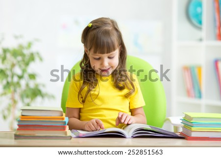 Happy child girl learning to read in nursery
