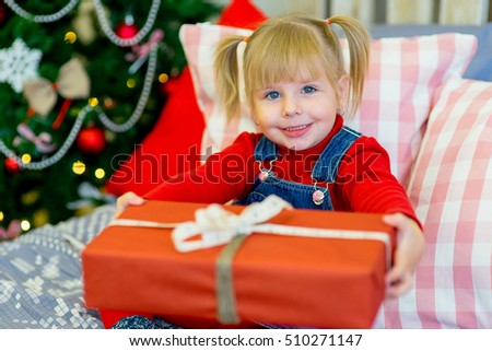 happy child girl near a decorated Christmas tree surprized by Christmas gifts