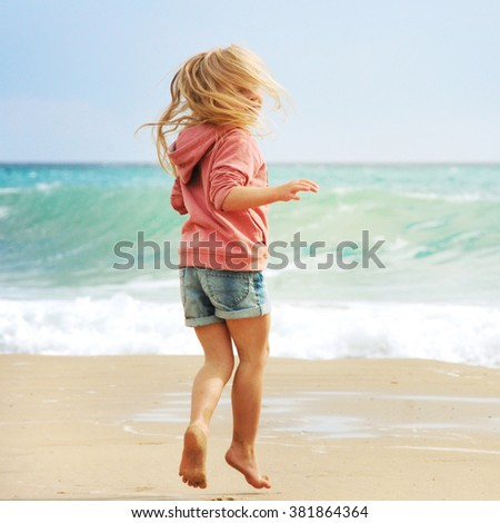 Happy child girl on a sea beach - stock photo